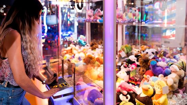 Mujer de lado jugando máquina arcade