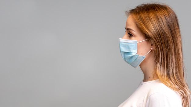 Mujer de lado con máscara y espacio de copia