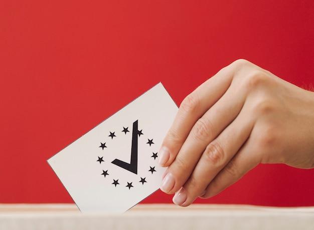 Mujer de lado poniendo una tarjeta de votación europea en una caja