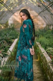 Mujer de lado posando en una casa verde mirando a cámara