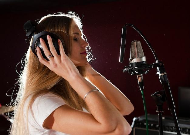 Mujer de lado preparándose para cantar su parte