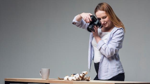 Mujer de lado sosteniendo una cámara profesional y tomando fotos de comida