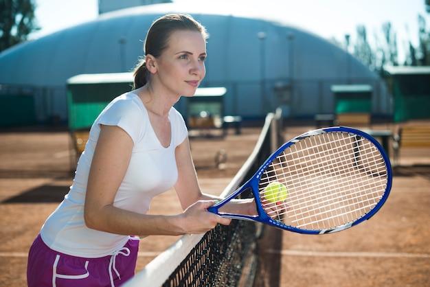 Mujer de lado sosteniendo el cohete de tenis