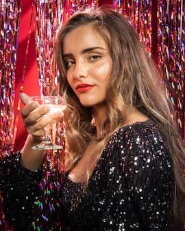 Mujer de lado sosteniendo una copa de champán