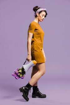 Mujer de lado sosteniendo el megáfono y flores