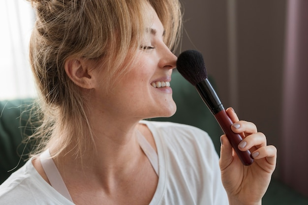 Mujer de lado usando un pincel de maquillaje