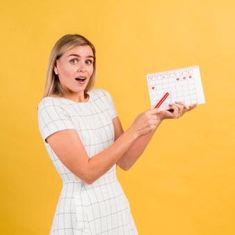 Mujer de lado en vestido blanco con calendario de período