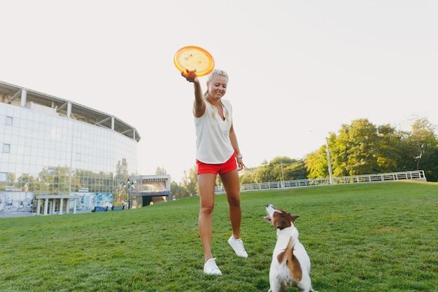 Mujer lanzando un disco volador naranja a un pequeño perro gracioso, que lo atrapa en la hierba verde. pequeña mascota jack russel terrier jugando al aire libre en el parque. perro y dueño al aire libre.