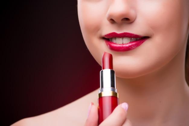 Mujer con lápiz labial rojo en concepto de belleza