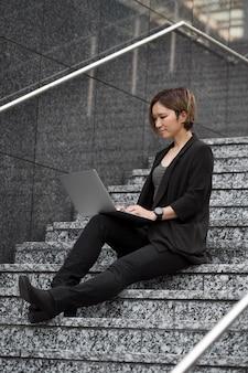 Mujer con laptop en escaleras full shot