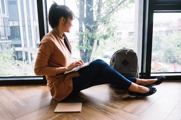 Mujer con laptop mirando por la ventana