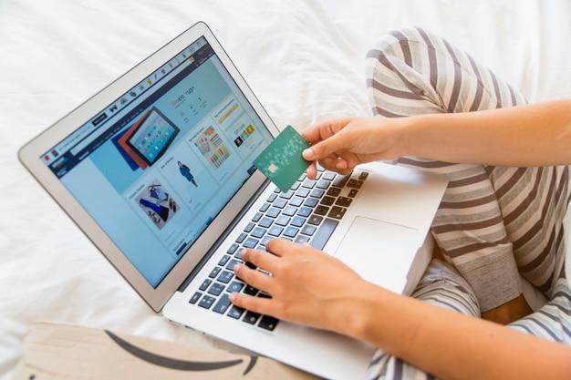 Mujer con laptop y tarjeta de crédito.