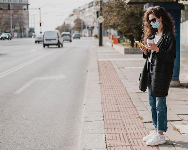 Mujer larga vista esperando en la estación de autobuses