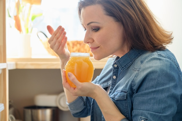 Mujer con lata de miel dorada orgánica natural fresca