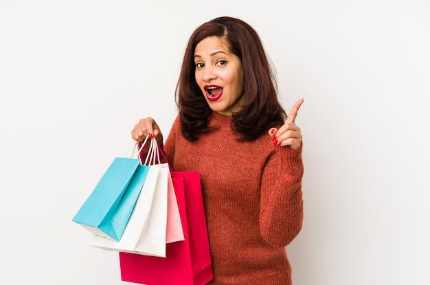 Mujer latina de la edad media que sostiene bolsos de compras aislados teniendo una idea, concepto de la inspiración.