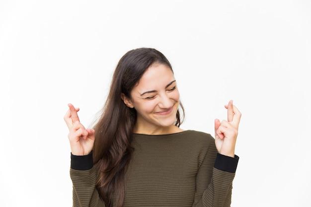 Mujer latina feliz emocionada manteniendo los dedos cruzados