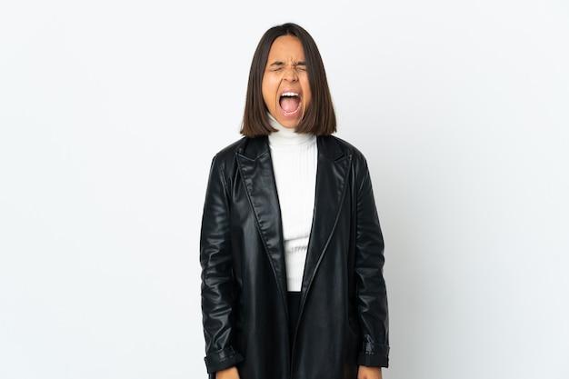 Mujer latina joven aislada en la pared blanca gritando al frente con la boca abierta