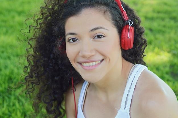 Mujer latina joven con los auriculares en un parque.