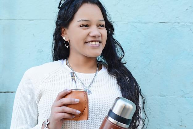 Mujer latina joven que bebe té tradicional del compañero del yerba.