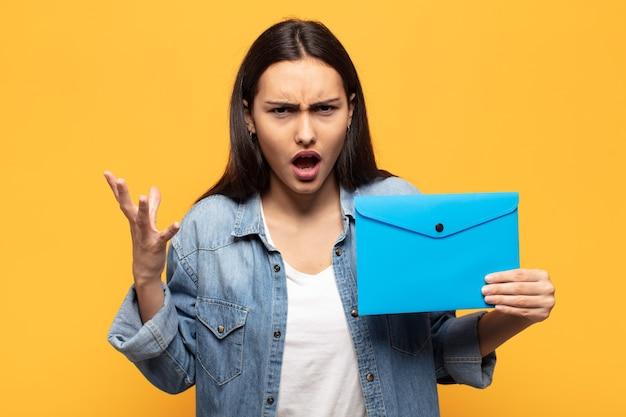 Mujer latina joven que parece enojado, molesto y frustrado gritando