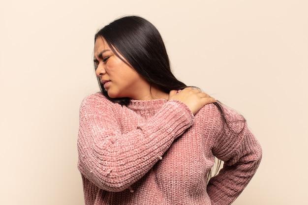 Mujer latina joven que se siente cansada, estresada, ansiosa, frustrada y deprimida, que sufre de dolor de espalda o cuello