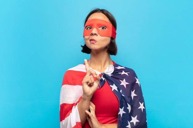 Mujer latina joven que se siente como un genio sosteniendo el dedo con orgullo en el aire después de darse cuenta de una gran idea, diciendo eureka