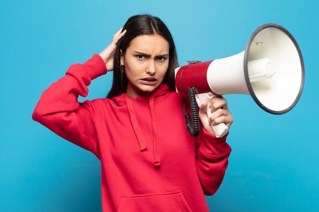 Mujer latina joven que se siente estresada, preocupada, ansiosa o asustada, con las manos en la cabeza, presa del pánico por el error