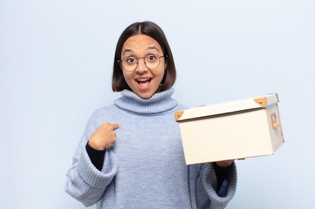 Mujer latina joven que se siente feliz, sorprendida y orgullosa, apuntando a sí misma con un emocionado