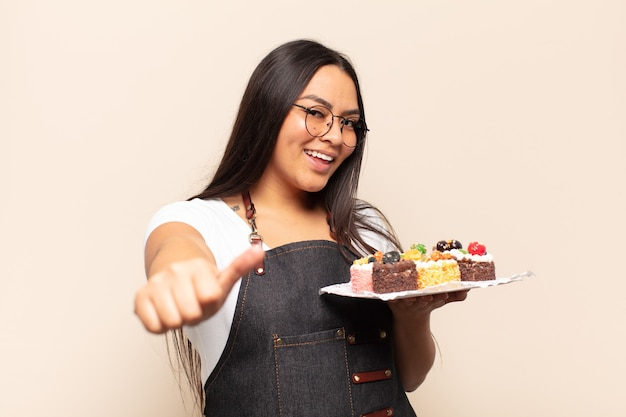 Mujer latina joven que se siente orgullosa, despreocupada, segura y feliz, sonriendo positivamente con los pulgares hacia arriba