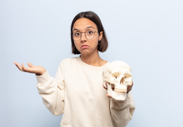 Mujer latina joven que se siente perpleja y confundida, dudando, ponderando o eligiendo diferentes opciones con expresión divertida