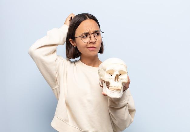 Mujer latina joven que se siente perpleja y confundida, rascándose la cabeza y mirando hacia un lado