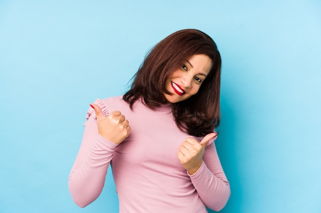 Mujer latina de mediana edad aislada levantando ambos pulgares, sonriente y confiado.