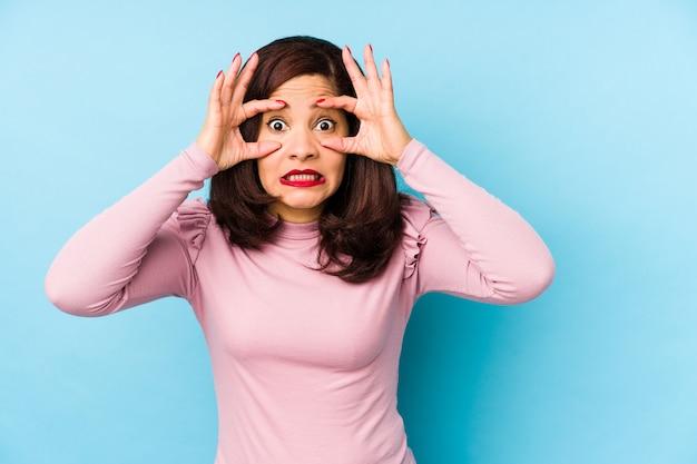 Mujer latina de mediana edad aislada manteniendo los ojos abiertos para encontrar una oportunidad de éxito.