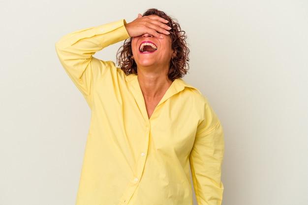 La mujer latina de mediana edad aislada sobre fondo blanco cubre los ojos con las manos, sonríe ampliamente esperando una sorpresa.