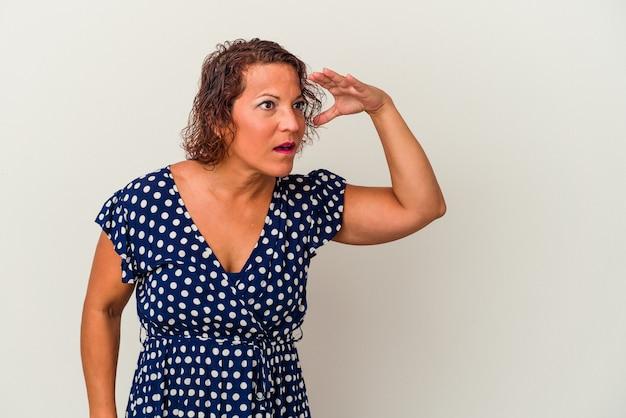 Mujer latina de mediana edad aislada sobre fondo blanco mirando lejos manteniendo la mano en la frente.