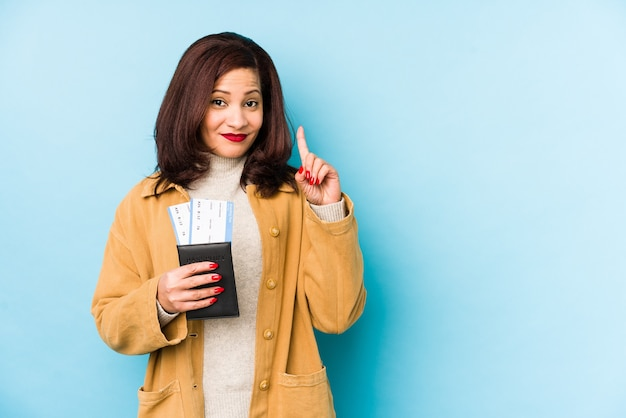 Mujer latina de mediana edad sosteniendo un pasaporte aislado mostrando el número uno con el dedo.