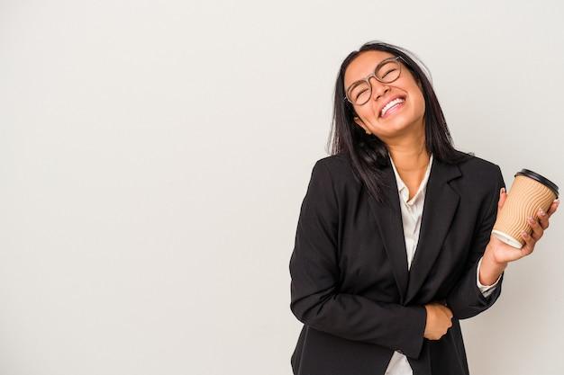 Mujer latina de negocios joven sosteniendo un café para llevar aislado sobre fondo blanco riendo y divirtiéndose.