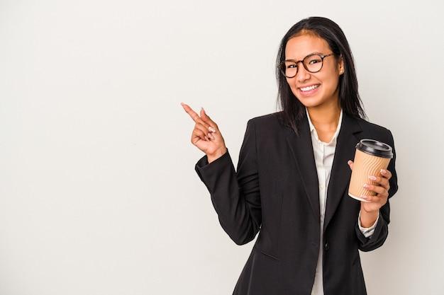 Mujer latina de negocios joven sosteniendo un café para llevar aislado sobre fondo blanco sonriendo y apuntando a un lado, mostrando algo en el espacio en blanco.