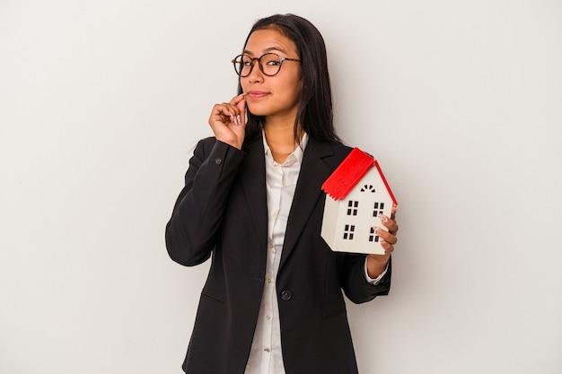 Mujer latina de negocios joven sosteniendo una casa de juguete aislada sobre fondo blanco con los dedos en los labios manteniendo un secreto.