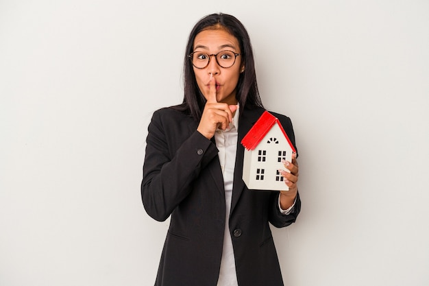 Mujer latina de negocios joven sosteniendo una casa de juguete aislada sobre fondo blanco manteniendo un secreto o pidiendo silencio.