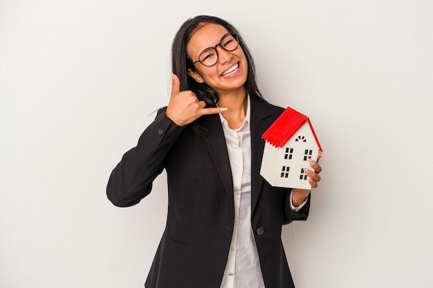 Mujer latina de negocios joven sosteniendo una casa de juguete aislada sobre fondo blanco mostrando un gesto de llamada de teléfono móvil con los dedos.