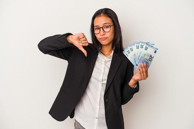 Mujer latina de negocios joven sosteniendo facturas café aislado sobre fondo blanco mostrando un gesto de aversión, pulgares hacia abajo. concepto de desacuerdo.