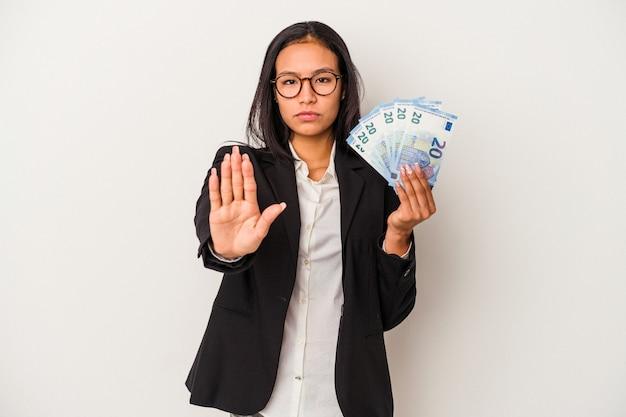 Mujer latina de negocios joven sosteniendo facturas café aislado sobre fondo blanco de pie con la mano extendida mostrando la señal de stop, impidiéndote.