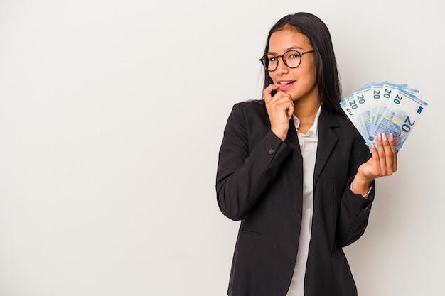 Mujer latina de negocios joven sosteniendo facturas café aislado sobre fondo blanco relajado pensando en algo mirando un espacio de copia.