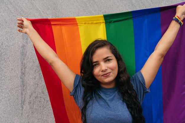 Mujer latina de pie en la calle con la bandera lgtb. concepto lgbt