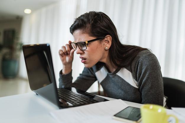 Mujer latina con problemas de visión tratando de leer contenido en línea en una computadora portátil