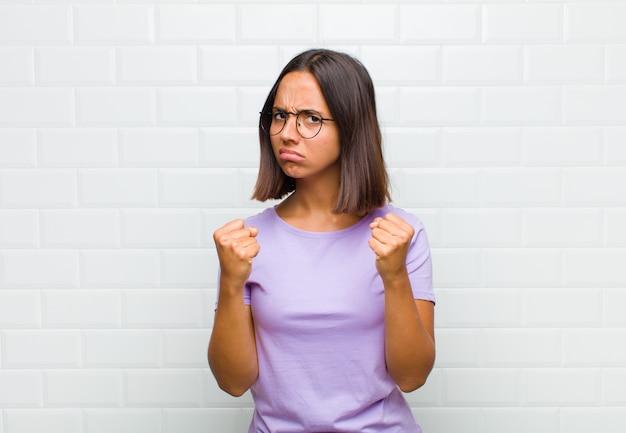 Mujer latina que parece segura, enojada, fuerte y agresiva, con puños listos para pelear en posición de boxeo