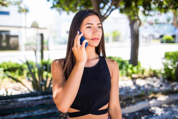 Mujer latina sentada en un banco en el parque verde el día de verano y hablando por teléfono inteligente