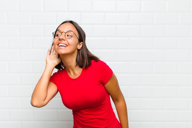 Mujer latina sonriendo, mirando con curiosidad a un lado, tratando de escuchar chismes o escuchar un secreto