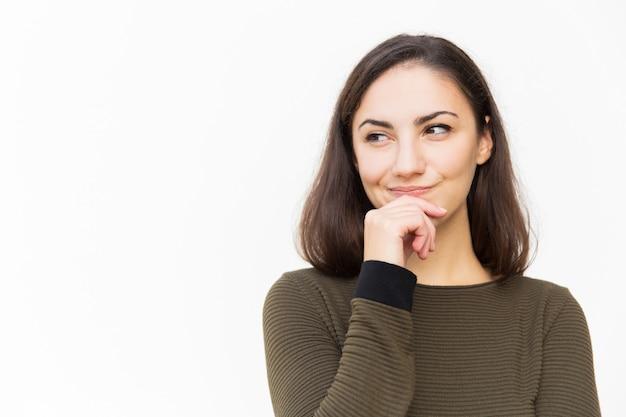 Mujer latina sonriente alegre que toca la barbilla